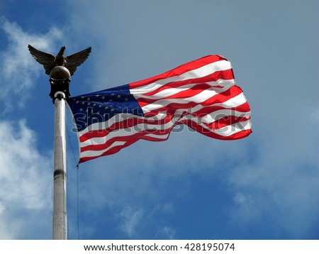 Detail of American flag. Taken in Washington D. C. Banner fluttering in the wind on nice summer day. Cloudy skies in the background. - stock photo
