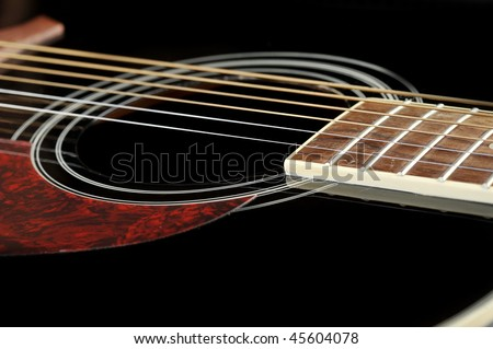 Detail of an acoustic black guitar with the strings and the sound hole