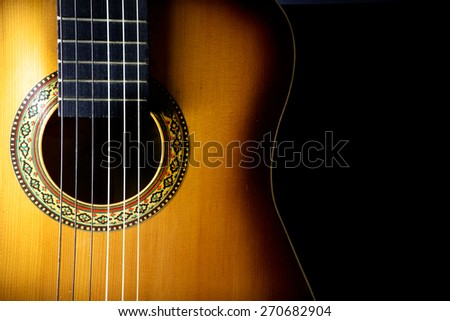 Detail of an acoustic guitar on black background - stock photo