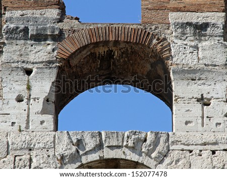 detail of an ancient Arch of the Colosseum and the blue sky of Rome in Italy - stock photo