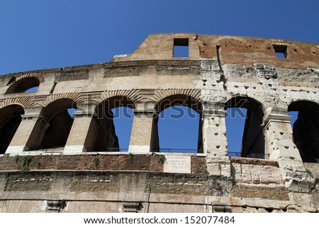 detail of an ancient Arch of the Colosseum in Rome Italy and blue sky - stock photo