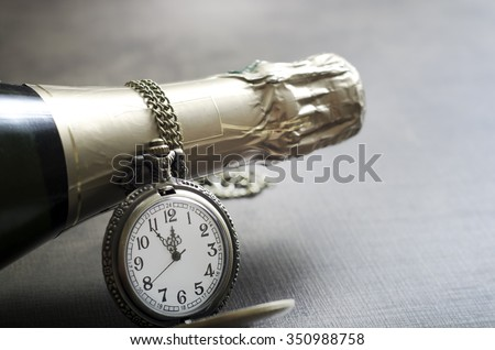 Detail of an antique pocket watch with chain and champange bottle neck with the hands of the watch approaching midnight