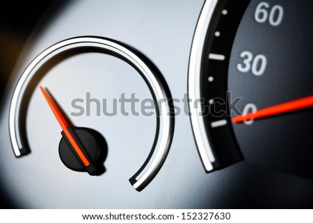 Detail of an empty gauge with a red pointing needle - stock photo