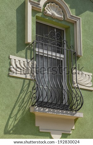 detail of an old building and a window with metal grille - stock photo