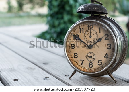 Detail of an old clock in an environment with plants