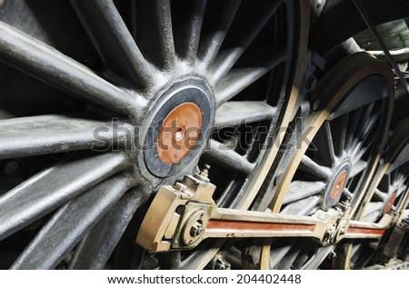 Detail of an old steam locomotive drive wheels and coupling rods. Shallow DOF. - stock photo