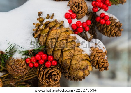 Detail of an outside Christmas cone wreath covered in snow - stock photo