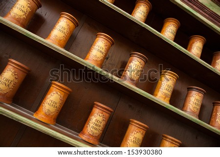 Detail of ancient drug store (pharmacy) with wooden containers on shelves. - stock photo