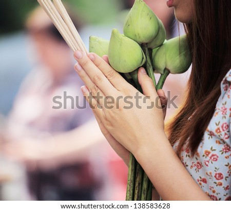 detail of asian woman praying buddha with lotus flower and incense stick - stock photo