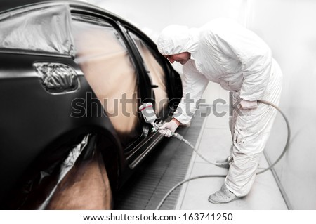 Detail of automotive engineer, mechanic painting a black car in workshop - stock photo
