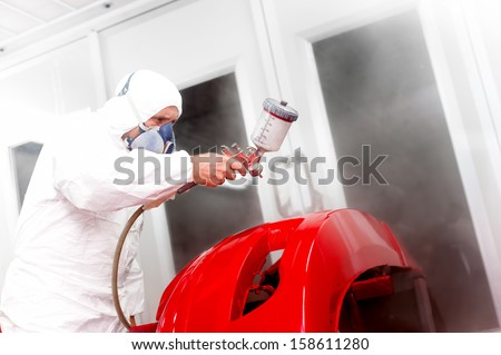 Detail of automotive engineer, mechanic painting a red bumper of a car in workshop