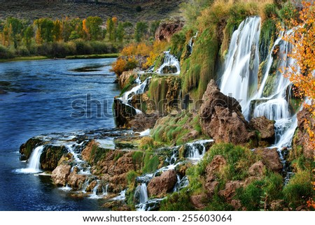 Detail of autumn waterfall with orange leaves - stock photo