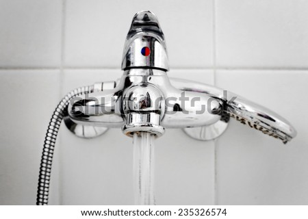detail of bath steel faucet - stock photo