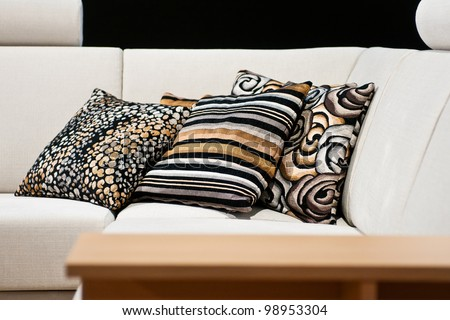 Detail of beige fabric sofa with cushions in gold, silver and black decor - stock photo