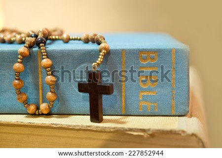 detail of bible with rosary on the table - stock photo