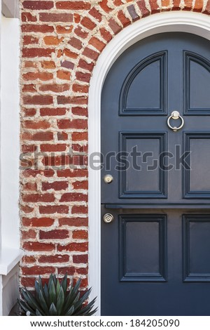 Detail of blue door to classic brownstone home. Detail of a lacquered blue front door to a classic brownstone family home. Door is featured under brick arch, with door knocker, and a plant.  - stock photo