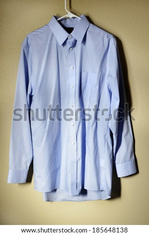 Detail of blue dress shirt hanging on hanger with light