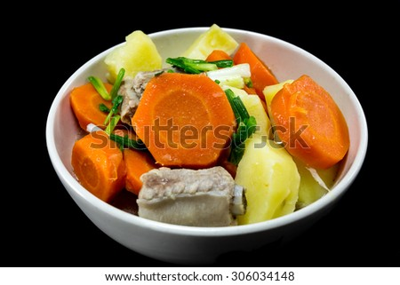 Detail of bowl with potato soup with pork rib and carrot on black background. Vietnam food