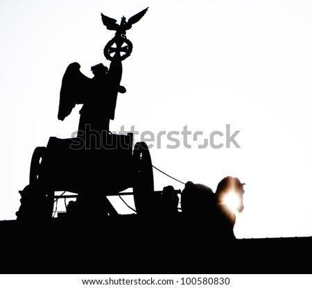 Detail of Brandenburg Gate and the Quadriga bronze statue. It is called Brandenburger Tor and it's one of the few monuments that survived in the defeated capital town of Berlin after second world war. - stock photo