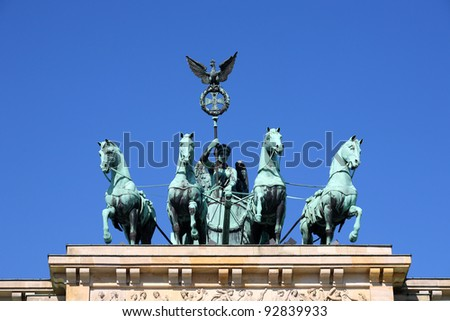 Detail of Brandenburg Gate and the Quadriga bronze statue. It is called Brandenburger Tor and it's one of the few monuments that survived in the defeated capital town of Berlin after second world war - stock photo