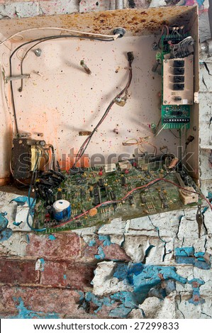 Detail of broken security alarm box in abandoned building, on brick wall covered in peeling paint - stock photo