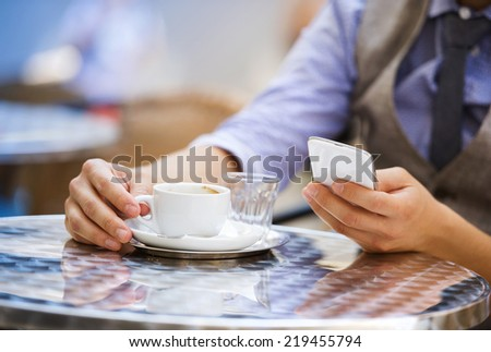 Detail of businessman drinking espresso coffee in the city cafe during lunch time and using mobile phone - stock photo