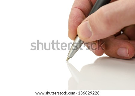Detail of businessman hand holding a pen on a white table with reflection.