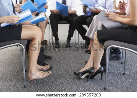 Detail Of Businesspeople Seated In Circle At Company Seminar - stock photo