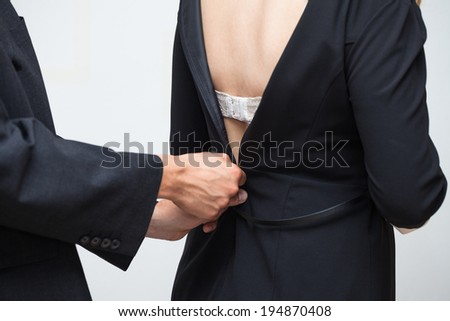Detail of businesswoman and businessman unzipping her dress. - stock photo