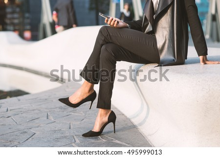 Detail of businesswoman portrait outdoors in Milan while using smart phone.