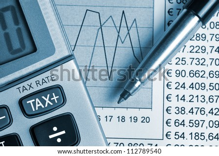 Detail of calculator, focusing the TAX key, next to a sheet of paper with numbers and a metal pen - stock photo