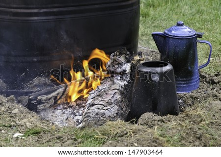 Detail of campfire, with burning log between two coffeepots and a tub of water, at Confederate encampment before reenactment of battle in American Civil War (1861-1865) - stock photo