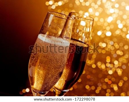 detail of champagne flutes with golden bubbles on warm light bokeh background with space for text - stock photo