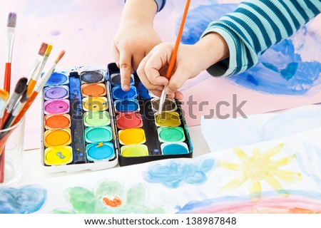 Detail of child's hand painting with watercolor - stock photo
