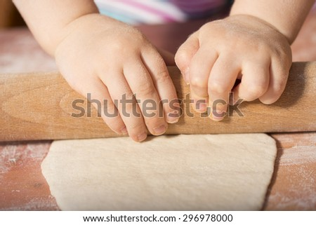 Detail of children hands kneading dough with wooden roller pin - stock photo