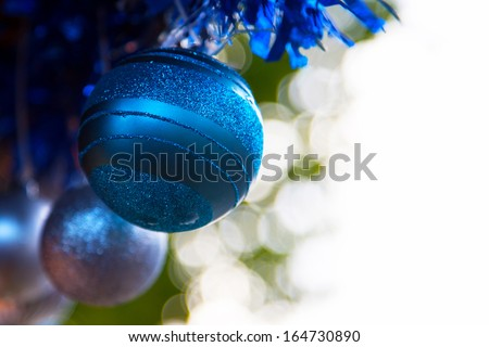 Detail of christmas baubles with tinsel. Selective focus and bokeh background. Room for you text. - stock photo