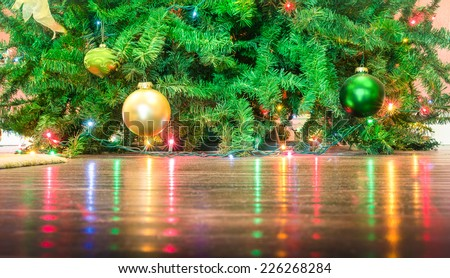 Detail of Christmas tree decorations with lights reflections on the floor - Cropped composition for holidays background - stock photo