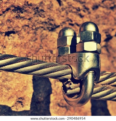Detail of chrome screws snap hooks and grommets at and of rope. Iron twisted rope fixed together by screws snap hooks. Detail of rope end anchored at sandstone rock  - stock photo