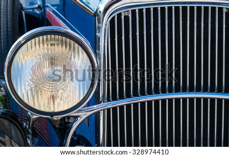 Detail of chromed plated old car front light and radiator - stock photo