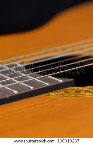 Detail of classic guitar (Spanish), against black background.