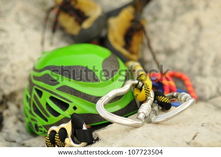 Detail of climbing helmet, carabiners and shoes lying on rock, focus on carabiner - stock photo