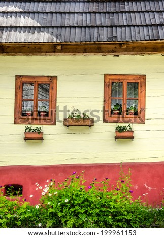 Detail of colorful windows with flowers on old traditional house, Vlkolinec village, Slovakia
