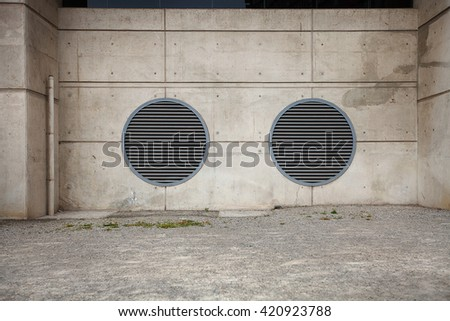 Detail of concrete building walls and large circular air vents