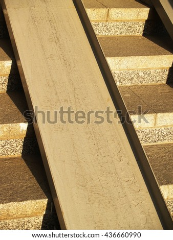 Detail of concrete stairway with metallic ramp for wheelchairs and pushchairs - stock photo