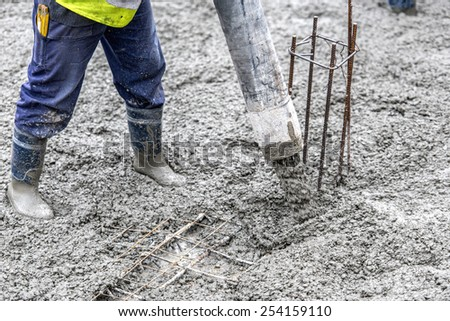 Detail of construction site - worker pouring cement and concrete with pump tube - stock photo
