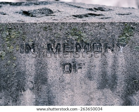 Detail of corroded gravestone with the words In Memory of  in cemetery on gloomy day in black and white - stock photo
