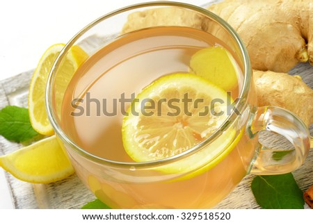 detail of cup of ginger tea with lemon and fresh ginger on wooden cutting board - stock photo