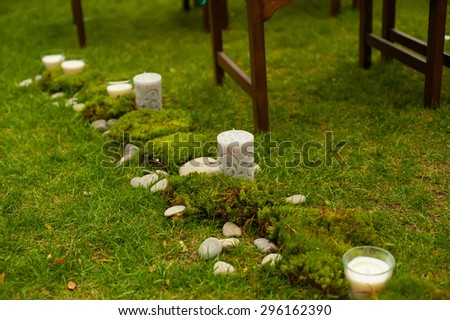 Detail of decor. Wedding ceremony. Beautiful candles in glass candlesticks.  - stock photo