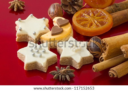 Detail of delicious Christmas cookies with spices on red Holiday background