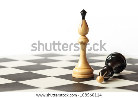 Detail of Detail of black and white kings on chessboard with white background - stock photo